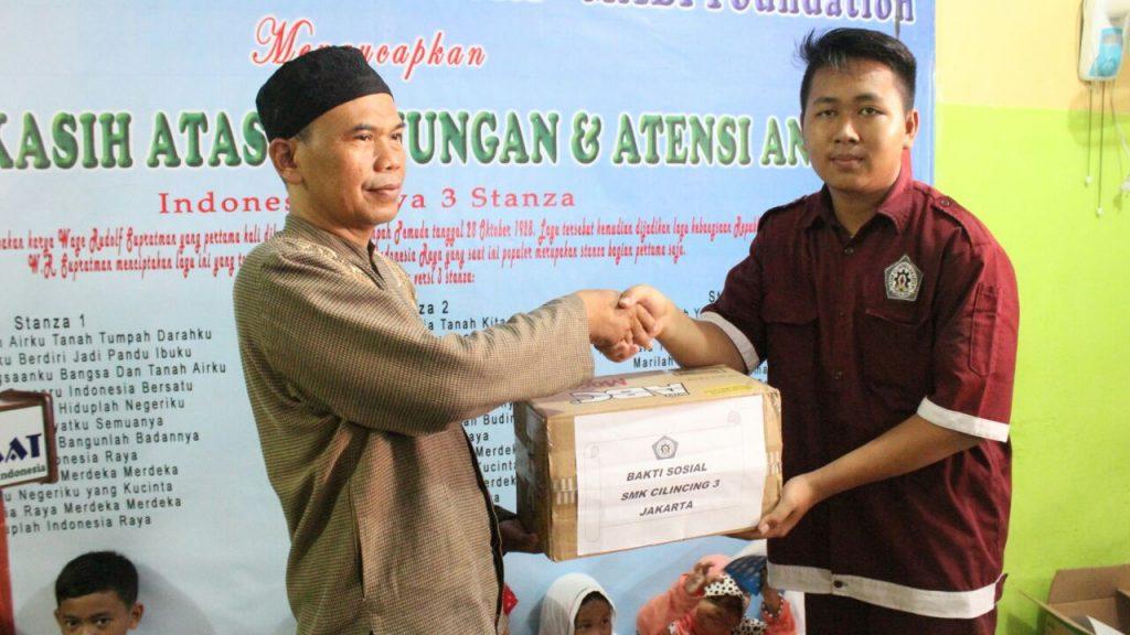Anggota ROHIS (Rohani Islam) SMK 3 Cilincing Menyerahkan Bantuan Secara Simbolis